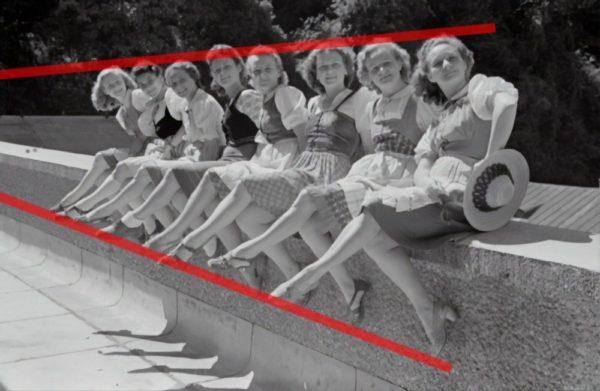 Mulheres sentadas em uma parede em uma fileira, mostrando a perspectiva de um ponto com o PF bem à esquerda.